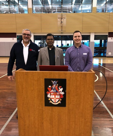 Fr. Lalit Tirkey SJ (centre) at St. Paul's High School, Winnipeg, with Fr Len Altilia SJ, President (at left), and Rob Lewin, Principal. (Photo: CJI)
