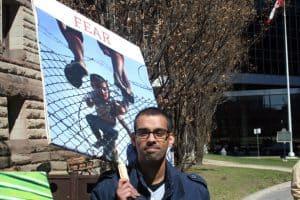 """Kenneth Vaz near Old City Hall with CJI's """"fear"""" placard"""