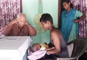 Dr Ramesh Anand prepares to examine a young couple's baby at Jesu Ashram.